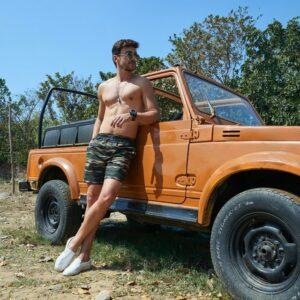 Stylish man enjoying summer outside next to jeep